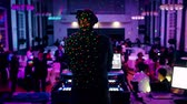 паз : Rear view of DJ mixing dancing in front his turntables and mixer and laptop during party wedding - illumination with laser light of his back and large room with guests