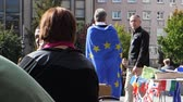 göç : STRASBOURG, FRANCE - CIRCA 2017: Man wearing European union blue flag with stars at protest in central Strasbourg during the Day of Europe - slow motion Stok Video
