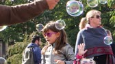 sopro : STRASBOURG, FRANCE - CIRCA 2017: Girls jumping and playing with the soap bubbles in central square of Strasbourg, European Capital in Place Kleber slow motion cinematic