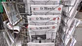 first person view : PARIS, FRANCE - MAR 15, 2018: Stack of French Le monde newspaper with portrait of Stephen Hawking the English theoretical physicist, cosmologist dead on 14 March 2018 outdoor press kiosk Stock Footage