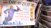 morrer : PARIS, FRANCE - CIRCA 2018: Man POV buying press kiosk stand with Die Zeit German newspaper with caricature of Donald Trump and text Trump Attacks Germany