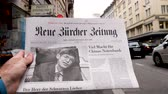 first person view : PARIS, FRANCE - MAR 15, 2018: Showing Swiss Neue Burcher Zeitung newspaper with portrait of Stephen Hawking the English theoretical physicist, cosmologist dead on 14 March 2018 outdoor press kiosk