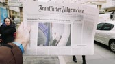 first person view : PARIS, FRANCE - MAR 15, 2017: Man reading buying German Frankfurter Allgemeine Zeitung newspaper at press kiosk featuring Angela Dorothea Merkel re election as Chancellor of Germany cinematic slow motion pedestrians