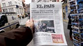 físico : PARIS, FRANCE - MAR 15, 2018: Slow motion Male hand holding Spanish El Pais newspaper with portrait of Stephen Hawking the English theoretical physicist, cosmologist dead on 14 March 2018 outdoor press kiosk Vídeos