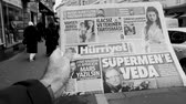 first person view : PARIS, FRANCE - MAR 15, 2018: Turkish Hurriyet newspaper with portrait of Stephen Hawking the English theoretical physicist, cosmologist dead on 14 March 2018 outdoor press kiosk - black and white, slow motion Stock Footage