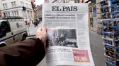 buy press : PARIS, FRANCE - MAR 15, 2018: City slow motion with Male hand holding Spanish El Pais newspaper with portrait of Stephen Hawking the English theoretical physicist, cosmologist dead on 14 March 2018 outdoor press kiosk