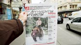 dziennikarz : PARIS, FRANCE - MAR 15, 2018: Argumenty i Fakty Russian newspaper featuring the photograph of Vladimir Putin on a Siberian grizzly bear before Russian Elections street slow motion
