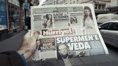 first person view : PARIS, FRANCE - MAR 15, 2018: Turkish Hurriyet newspaper with portrait of Stephen Hawking the English theoretical physicist, cosmologist dead on 14 March 2018 outdoor press kiosk slow motion street women Stock Footage