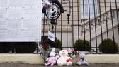 symbol of respect : STRASBOURG, FRANCE - MAR 28, 2018: Tilt-up to flowers, toys at entrance of Russian Consulate Embassy mourning of victims of fire at Zimnyaya Vishnya Winter Cherry shopping centre Kemerovo Stock Footage