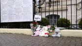 stožár : STRASBOURG, FRANCE - MAR 28, 2018: Pedestrian walking near toys and flowers near Russian Consulate Embassy mourning victims fire at Zimnyaya Vishnya Winter Cherry shopping centre Kemerovo slow motion