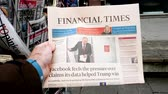 consulate : PARIS, FRANCE - MAR 19, 2017: Man reading buying British Financial Times newspaper at press kiosk featuring Russian presidential election from 2018 with the winner Vladimir Putin Stock Footage