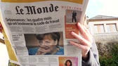 paryż : PARIS, FRANCE - SEP 24, 2017: Woman reading latest newspaper Le Monde with portrait of Angela Merkel before the election in Germany for the Chancellor of Germany, the head of the federal government Wideo