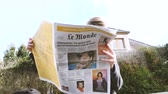 bajnok : PARIS, FRANCE - SEP 24, 2017: View from below of woman reading latest newspaper Le Monde with portrait of Angela Merkel before the election in Germany for the Chancellor of Germany, the head of the federal government
