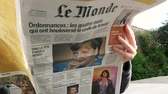 almanca : PARIS, FRANCE - SEP 24, 2017: View from below of curious woman reading latest newspaper Le Monde with portrait of Angela Merkel before the election in Germany for the Chancellor of Germany Stok Video