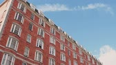 flats : LONDON, UNITED KINGDOM - CIRCA 2017: Tilt of from busy street to modern British apartment building view from below with blue peaceful sky and scattered clouds - visiting and living in London Stock Footage
