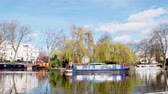 waterway : LONDON, UNITED KINGDOM - CIRCA 2018: Little Venice canal neighborhood business people pedestrians walking on a warm spring day with view to the Robert Brownings Island. It is a Central London Narrowboat in picturesque and calm area Stock Footage