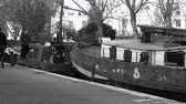 captain : LONDON, UNITED KINGDOM - CIRCA 2018: Little Venice canal neighborhood with adult male captain anchoring the ship barges to shore with pedestrians walking nearby - black and white footage 4k