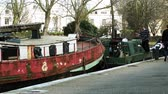 Венеция : LONDON, UNITED KINGDOM - CIRCA 2018: Little Venice canal neighborhood with adult male captain anchoring the ship barges to shore with pedestrians walking nearby
