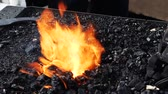 rycerz : zoom out of slow motion - blacksmith forging fire with black coals and steel part in the burning fire instruments and tools