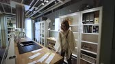 sala de exposição : PARIS, FRANCE - CIRCA 2018: Modern IKEA furniture store woman customer browsing through diverse furniture, decoration warehouse goods - new kitchen furniture with all the accessories