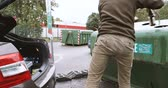 recyclable : PARIS, FRANCE - CIRCA 2018: Man taking from car trunk glass waste bottles for recycling at facility with different glass packaging bottle waste. waste management dechetterie in France - time lapse fast motion