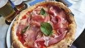 базилик : Pan over delicious well made pizza in pizzeria restaurant next to two beers - San Marzano DOP tomato, Campania buffalo mozzarella, 18 months Parma raw ham, basil and black pepper Стоковые видеозаписи
