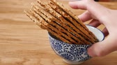 düşük kalorili : Man hand taking from Japanese bowl with healthy brown rye bread crisps on a wooden cutting board