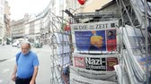 almanca : PARIS, FRANCE - JUN 12, 2017: City slow motion man in front of Die Zeit at press kiosk German newspaper with Donald Trump and Nazi message on the Bild magazine-