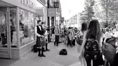 celta : Windsor, United Kingdom - May 19, 2018: Two pipers plays the bagpipes windpipe for money on street during Royal Wedding with people admiring old traditional music during Royal Wedding black and white Vídeos