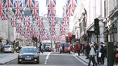 taksi : LONDON, UNITED KINGDOM - MAY 18, 2018: Pedestrians near bus station and Volkswagen car under Union Jack Flags on Regent Street Royal Wedding between Prince Harry and Meghan Markle cinematic flare