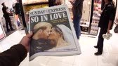 tál : LONDON, UK - MAY 20, 2018: POV The Sunday Express front cover newspaper British press kiosk Eurostar Train Station featuring portraits of Prince Harry and Meghan Markle Royal Wedding So In Love Stock mozgókép