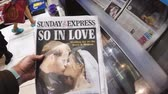 tál : LONDON, ENGLAND - MAY 20, 2018: POV The Sunday Express front cover newspaper British press kiosk featuring portraits of Prince Harry and Meghan Markle following the Royal Wedding So In Love cinematic Stock mozgókép