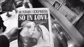 tál : LONDON, ENGLAND - MAY 20, 2018: POV The Sunday Express front cover newspaper in British kiosk featuring portraits Prince Harry and Meghan Markle following Royal Wedding So In Love - black and white Stock mozgókép