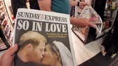 tál : LONDON, UK - MAY 20, 2018: Crowd reading The Sunday Express front cover newspaper British press kiosk featuring portraits of Prince Harry and Meghan Markle Royal Wedding So In Love