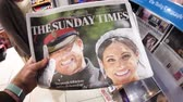 harry : LONDON, ENGLAND - MAY 20, 2018: POV The Sunday Express front cover newspaper in British press kiosk featuring portraits of Prince Harry and Meghan Markle following the Royal Wedding Stock Footage