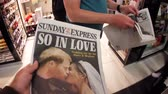 princ : LONDON, UK - MAY 20, 2018: Crowd reading The Sunday Express front cover newspaper British press kiosk featuring portraits of Prince Harry and Meghan Markle Royal Wedding So In Love