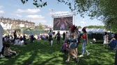 harry : WINDSOR, UNITED KINGDOM - MAY 19, 2018: Crowd of people watching the Royal Wedding via a large screen in Long Road park in Windsor during Prince Harry and Meghan Markle wedding - live broadcast