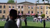 harry : WINDSOR, BERKSHIRE, UNITED KINGDOM - MAY 19, 2018: Adelaide Terrace building with UK US and Canada flags on facade and crowd celebration during the royal couple marriage celebration of Prince Harry and Meghan Markle Stock Footage