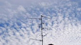 микроволновая печь : Beautiful cirrocumulus clouds on a summer afternoon with TV Television aerial antenna in the middle of the frame in 4k UHD cinematic mode