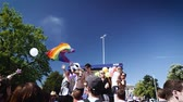 lésbica : STRASBOURG, FRANCE - JUN 10, 2017: Cinematic slow motion of majestic gay flag waving as gay friends are dancing on truck during gay pride in France, Strasbourg - annual LGBT pride FestiGays