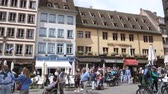 place kleber : STRASBOURG, FRANCE - CIRCA 2018: Place De La Cathedrale central square in Strasbourg with tourists pedestrians admiring the historic buildings with hotels and restaurants outdoor cafe area Stock Footage