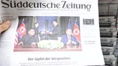 él : PARIS, FRANCE - JUNE 13, 2018: Holding German Suddeutsche Zeitung on stand newspaper at press kiosk showing on cover  U.S. President Donald Trump meeting North Korean leader Kim Jong-un in Singapore