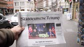 un : PARIS, FRANCE - JUNE 13, 2018: Slow motion - Holding German Suddeutsche Zeitung on stand newspaper at press kiosk showing on cover  U.S. President Donald Trump meeting North Korean leader Kim Jong-un Stock Footage
