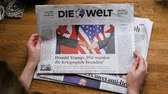 morrer : PARIS, FRANCE - JUNE 13, 2018: Woman reading German Die Welt newspaper in the office showing on cover  U.S. President Donald Trump meeting North Korean leader Kim Jong-un in Singapore Vídeos