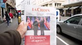 gazetecilik : PARIS, FRANCE - JUNE 13, 2018: Man buying La Croix newspaper at press kiosk showing on cover U.S. President Donald Trump meeting North Korean leader Kim Jong-un in Singapore - slow motion Stok Video
