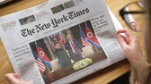 un : PARIS, FRANCE - JUNE 13, 2018: Woman reading The New York Times newspaper in the office showing on cover  U.S. President Donald Trump meeting North Korean leader Kim Jong-un in Singapore