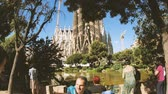 kuruluş : BARCELONA, SPAIN - CIRCA 2018: Tourist admiring Sagrada Familia Church built by Antoni Gaudi - international tourists taking photos selfies with the magnificent religious architecture from the Place de Gaudi