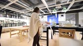 vitrin : PARIS, FRANCE - CIRCA 2018: Wide view of interior of IKEA furniture store with woman customer browsing multiple tables and chairs