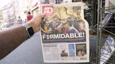 troféu : PARIS, FRANCE - JUL 16, 2018: Man buying Dutch newspaper announcing France champion title after French national football team won their FIFA World Cup 2018 with Breaking Formidable title slow motion Stock Footage