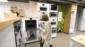 глобализация : PARIS, FRANCE - CIRCA 2018: Multiple contemporary IKEA furniture store with woman customer browsing through diverse furniture, decoration warehouse goods selecting perfect oven stove